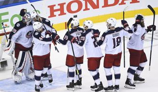 Columbus Blue Jackets goaltender Joonas Korpisalo (70) and teammates celebrate after defeating the Toronto Maple Leafs in an NHL hockey playoff game Sunday, Aug. 9, 2020, in Toronto. The Maple Leafs were eliminated from the playoffs. (Nathan Denette/The Canadian Press via AP)