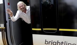 FILE - In this April 4, 2019, file photo Richard Branson, of Virgin Group, waves as he arrives on a Brightline train in West Palm Beach, Fla. The partnership between Richard Branson's Virgin and the private Florida passenger train service Brightline, which began with the British entrepreneur's trademark pizazz, has ended quietly with a whimper. Brightline announced in a monthly report that it has ended its affiliation with the Virgin Group and will stop its rebranding to Virgin Trains USA. (AP Photo/Lynne Sladky, File)