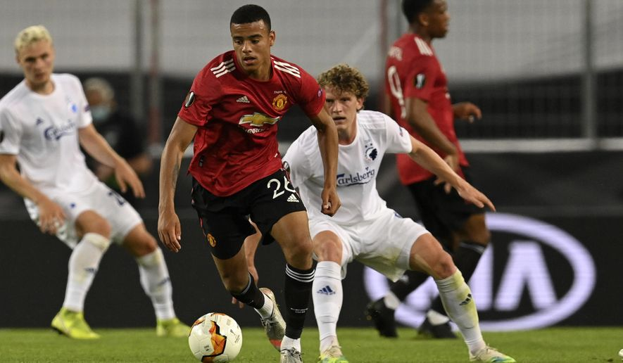 Manchester United's Mason Greenwood controls the ball during the Europa League quarter-final soccer match between Manchester United and Copenhagen at the Rhein Energie Stadium in Cologne, Germany, Monday, Aug. 10, 2020. (Sascha Steinbach/EPA via AP)