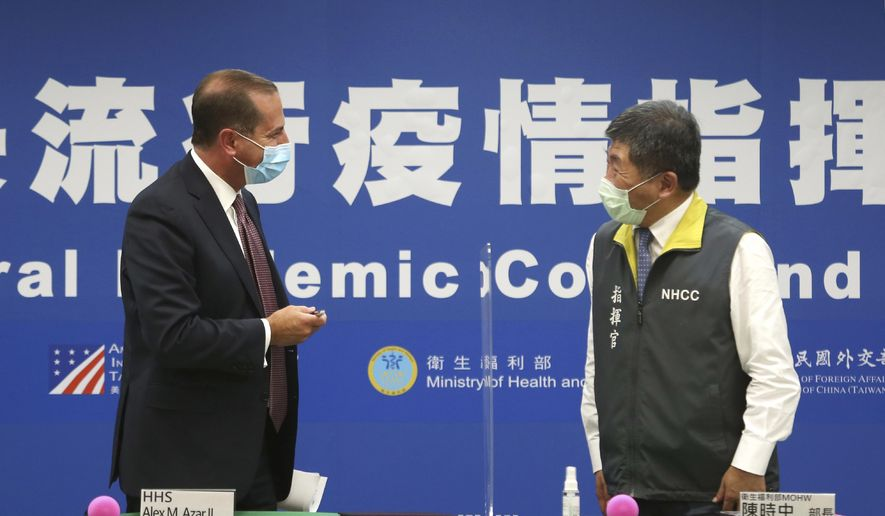 U.S. Health and Human Services Secretary Alex Azar, left, greets Taiwanese Minister of Health and Welfare Chen Shih-chung after the signing ceremony for a memorandum of understanding at the Central Epidemic Command Center in Taipei, Taiwan, Monday, Aug. 10, 2020. Azar arrived in Taiwan on Sunday in the highest-level visit by an American Cabinet official since the break in formal diplomatic relations between Washington and Taipei in 1979. (AP Photo/Chiang Ying-ying)