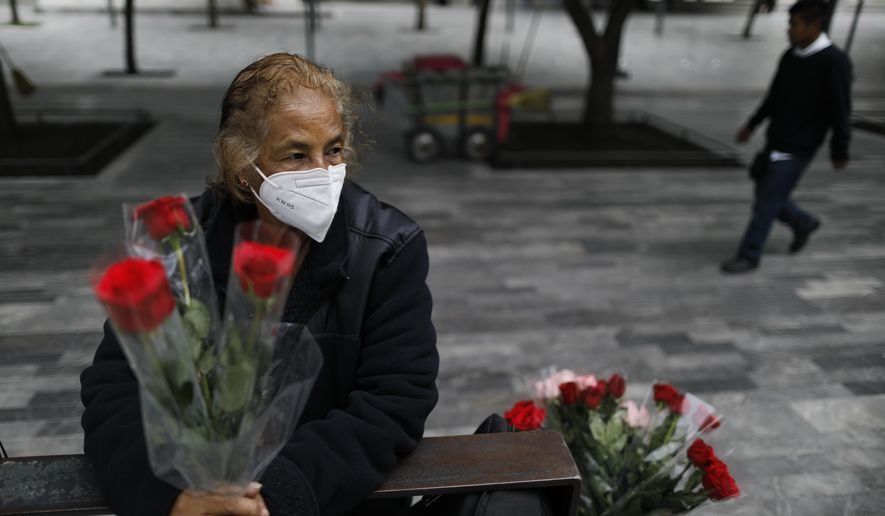 """Wearing a mask to curb the spread of the new coronavirus, Martha Gonzalez Reyes, 76, sells roses outside Metro Hidalgo in central Mexico City, Monday, Aug. 10, 2020. After four months staying at home, Gonzalez returned to selling on August 1, but she says business hasn't fully rebounded. """"People have less money to spend she says, and they don't want to go out and get infected.""""(AP Photo/Rebecca Blackwell)"""