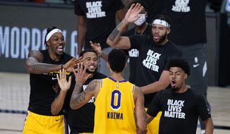Los Angeles Lakers' Kyle Kuzma (0) is congratulated by teammates after hitting a game-winning 3-pointer against the Denver Nuggets during the second half of an NBA basketball game Monday, Aug. 10, 2020, in Lake Buena Vista, Fla. The Lakers won 124-121. (AP Photo/Ashley Landis, Pool)  **FILE**