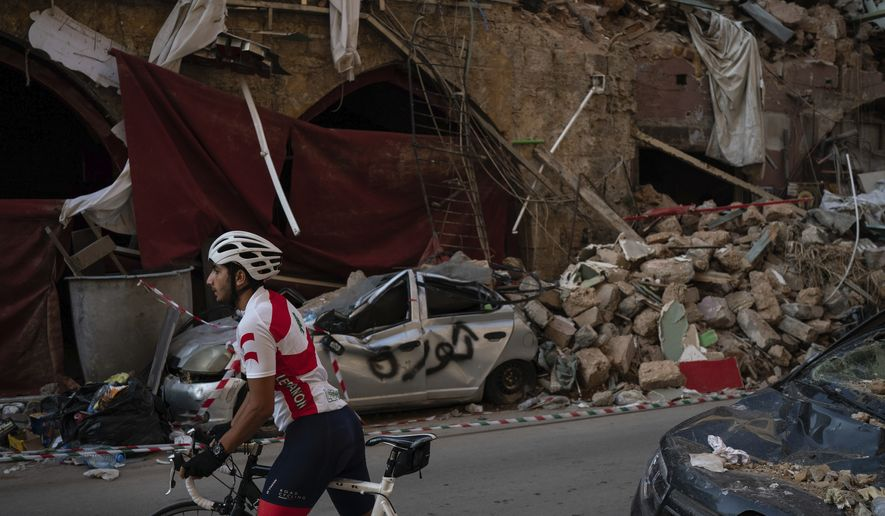 A cyclist rides past destroyed buildings and cars in a neighborhood near the site of last week's explosion that hit the seaport of Beirut, Lebanon, Tuesday, Aug. 11, 2020. (AP Photo/Felipe Dana)