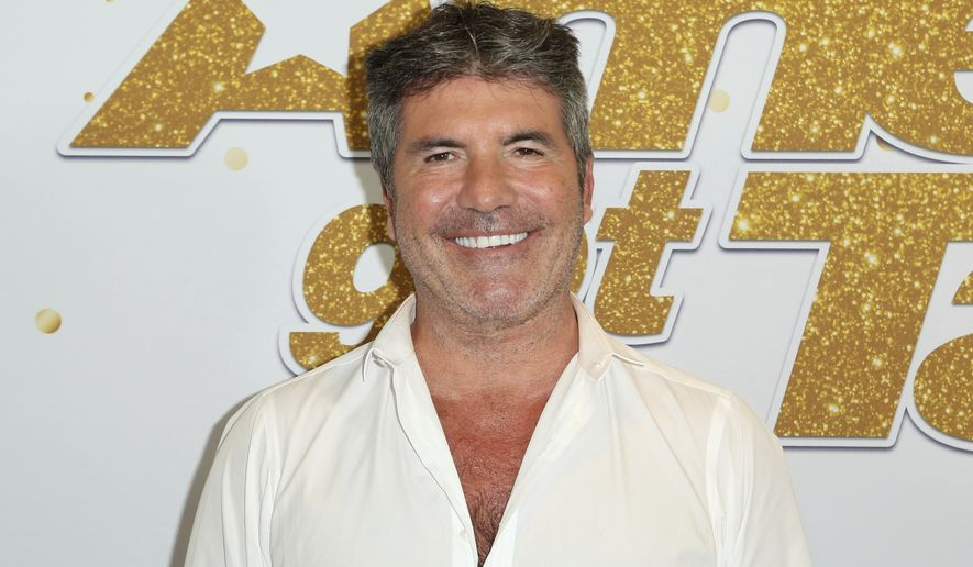 """In this Sept. 18, 2018, file photo, Simon Cowell arrives at the """"America's Got Talent"""" Season 13 Finale Show red carpet at the Dolby Theatre, in Los Angeles. America's Got Talent topped the ratings last week, but it faces the absence of Cowell, seriously injured in an electric bicycle accident. Cowell, the NBC talent contest's creator and linchpin of its judging panel, underwent surgery for a broken back last Saturday, Aug. 8, 2020, just before the show kicked off its live episodes this week. (Photo by Willy Sanjuan/Invision/AP, File)"""