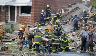 Baltimore City Fire Department carries a person out from the debris after an explosion in Baltimore on Monday, Aug. 10, 2020. Baltimore firefighters say an explosion has levelled several homes in the city. (AP Photo/Julio Cortez)