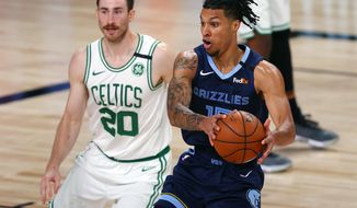 Memphis Grizzlies' Brandon Clarke (15) handles the ball as Boston Celtics' Gordon Hayward (20) defends during the second half of an NBA basketball game Tuesday, Aug. 11, 2020, in Lake Buena Vista, Fla. (AP Photo/Mike Ehrmann, Pool)