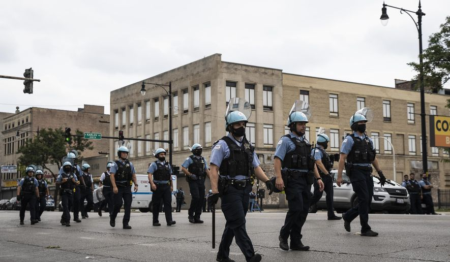 Chicago police officers respond to rioting near West Madison Street and South Karlov Avenue on the West Side, of Chicago, Monday, Aug. 10, 2020.  (Ashlee Rezin Garcia/Chicago Sun-Times via AP)