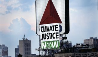 """CORRECTS PHRASE IN CAPTION TO CLIMATE JUSTICE NOW INSTEAD OF CLIMATE CHANGE NOW- Members of an environmental group hang a banner that reads """"CLIMATE JUSTICE NOW"""" on the iconic Citgo sign near Boston's Fenway Park in Kenmore Square on Monday, Aug. 8, 2020, in Boston. The group unfurled the banner Monday evening as the Red Sox began their game against the Tampa Bay Rays at Fenway. A spokesman for the group, Extinction Rebellion Boston, told The Boston Globe that it was hoping to bring attention to environmental issues. (Jim Davis/The Boston Globe via AP)"""