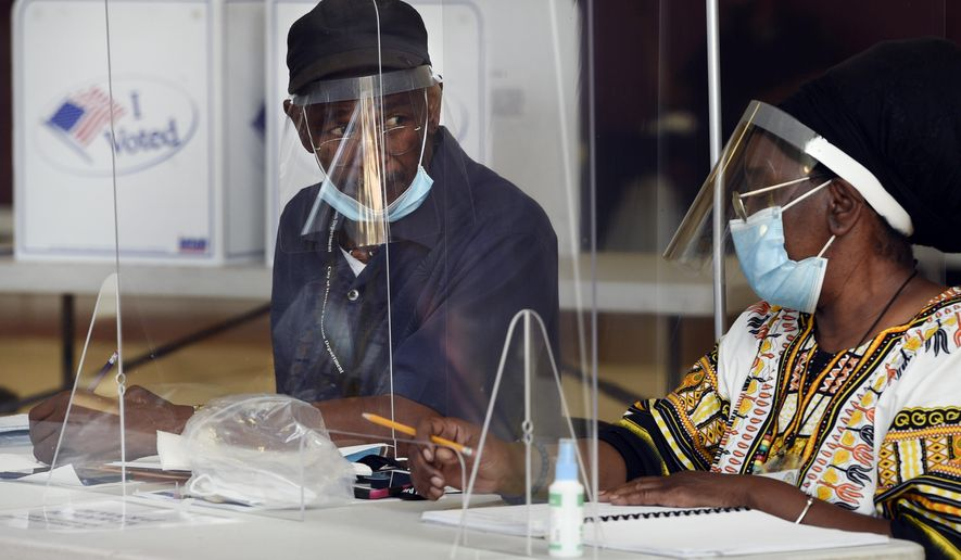 Volunteers Anthony Hall, left, and Patricia Nelson, right, prepare ballots at Rawson Elementary School, Tuesday, Aug. 11, 2020, in Hartford, Conn. (AP Photo/Jessica Hill)