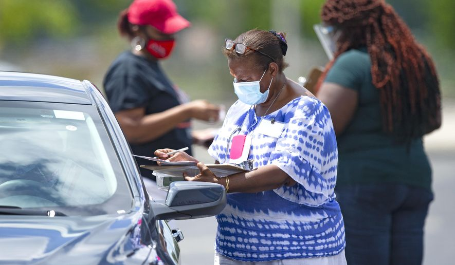 Polling workers help citizens to check in during early voting for primary election at the Miami Dade College North Campus located at 11380 NW 27th Avenue in Miami on Sunday, August 9, 2020. (David Santiago/Miami Herald via AP)