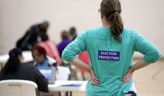 FILE - In this Nov. 8, 2016, file photo, poll watcher Jane Grimes Meneely, right, watches as voters sign in at the Martha O'Bryan Center community building in Nashville, Tenn. (AP Photo/Mark Humphrey, File)