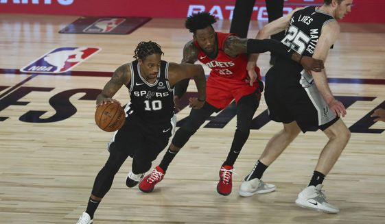 San Antonio Spurs forward DeMar DeRozan (10) drives past Houston Rockets forward Robert Covington (33) off a screen by center Jakob Poeltl (25) during the second half of a NBA basketball game Tuesday, Aug. 11, 2020, in Lake Buena Vista, Fla. (Kim Klement/Pool Photo via AP)