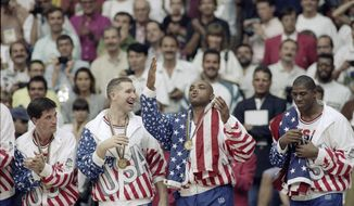 FILE - This Aug. 8, 1992, file photo shows, from left, USA's John Stockton, Chris Mullin, Charles Barkley and Magic Johnson rejoicing with their gold medals after beating Croatia 117-85 at the Summer Olympic Games in Barcelona. (AP Photo/John Gaps III, File)