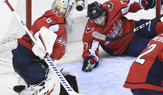 Washington Capitals right wing T.J. Oshie (77) makes a save and clears the puck away as Capitals goaltender Braden Holtby (70) watches during the second period of an NHL Eastern Conference Stanley Cup hockey playoff game in Toronto, Wednesday, Aug. 12, 2020. (Nathan Denette/The Canadian Press via AP)