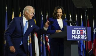 Democratic presidential candidate former Vice President Joe Biden retrieves his face mask from the podium as his running mate Sen. Kamala Harris, D-Calif., prepares to speak at a campaign event at Alexis Dupont High School in Wilmington, Del., Wednesday, Aug. 12, 2020. (AP Photo/Carolyn Kaster)