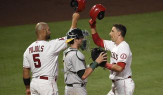 Los Angeles Angels' Jason Castro, right, celebrates with Albert Pujols, left, after hitting a three-run home run during the fourth inning of a baseball game as Oakland Athletics catcher Austin Allen looks on in Anaheim, Calif., Tuesday, Aug. 11, 2020. (AP Photo/Kelvin Kuo)