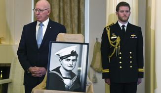 """Australian Governor-General David Hurley, left, makes an announcement in relation to the awarding of a Victoria Cross to sailor Edward """"Teddy"""" Sheean, photo at center, during a press conference at Government House in Canberra, Wednesday, Aug. 12, 2020. War hero Sheean will be awarded the nation's top military honor more than 77 years after he was killed while saving his shipmates. (Lukas Coch/AAP Image via AP)"""