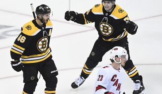 Boston Bruins center David Krejci (46) celebrates with teammate Jake DeBrusk (74) as Carolina Hurricanes left wing Brock McGinn (23) skates past during the third period of an NHL Eastern Conference Stanley Cup hockey playoff game in Toronto, Wednesday, Aug. 12, 2020. (Nathan Denette/The Canadian Press via AP)