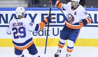 New York Islanders right wing Josh Bailey (12) celebrates his goal with teammate Brock Nelson (29) after scoring against the New York Islanders during the third period NHL Eastern Conference Stanley Cup playoff hockey game in Toronto on Wednesday, Aug. 12, 2020. (Nathan Denette/The Canadian Press via AP)