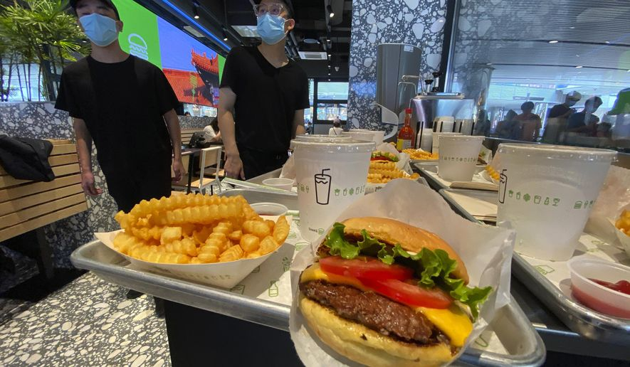Workers prepare to serve burgers at the first Beijing outlet for Shake Shack in Beijing on Wednesday, Aug. 12, 2020. The U.S. headquartered burger chain is opening its first Beijing restaurant at a time when China and the U.S. are at loggerheads over a long list of issues. (AP Photo/Ng Han Guan)