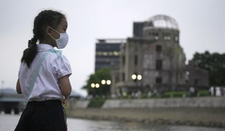 Saki Morioki, 5 years old, looks at paper lanterns floating along the Motoyasu River in front of the Atomic Bomb Dome, Thursday, Aug. 6, 2020. in Hiroshima, western Japan. Japan marked the 75th anniversary Thursday of the atomic bombing of Hiroshima. The official lantern event was cancelled to the public due to coronavirus but a small group of local representatives released some lanterns. (AP Photo/Eugene Hoshiko)