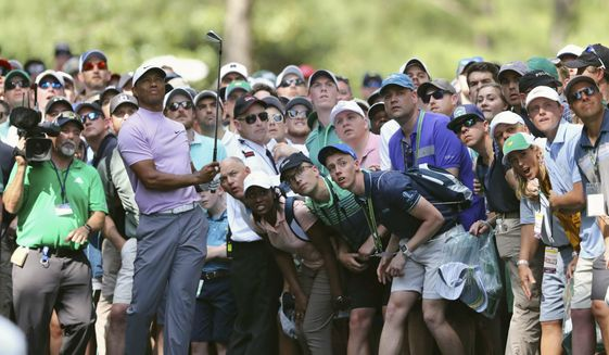 In this April 13, 2019, file photo, Tiger Woods hits from the gallery along the 11th fairway during the third round of the Masters golf tournament at Augusta National in Augusta, Ga. The Masters, the major known as much for the roars of the crowd as the raw beauty of Augusta National, will be on mute this year. The club decided Wednesday, Aug. 12, 2020, there will be no spectators. (Curtis Compton/Atlanta Journal-Constitution via AP) ** FILE **