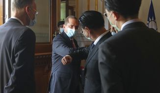 U.S. Health and Human Services Secretary Alex Azar, second from left, is greeted as he arrives at a memorial for former Taiwanese President Lee Teng-hui in Taipei, Taiwan, Wednesday, Aug. 12, 2020. Wednesday is the last day of Azar's schedule during the highest-level visit by an American Cabinet official since the break in formal diplomatic ties between Washington and Taipei in 1979. (Wang Teng-yi/Pool Photo via AP)