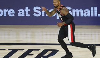Portland Trail Blazers guard Damian Lillard reacts after making a 3-point basket against the Dallas Mavericks during the second half of an NBA basketball game Tuesday, Aug. 11, 2020, in Lake Buena Vista, Fla. (Kim Klement/Pool Photo via AP)