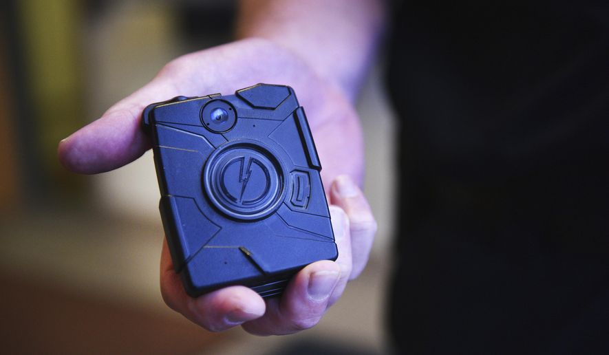 In this June 12, 2018, photo, Mitchell, S.D., Assistant Police Chief Michael Koster shows a first-generation body camera at the police department in Mitchell, S.D. Los Angeles County deputies, who make up the largest sheriff's department in the nation, will begin getting body-worn cameras in October, the sheriff announced Wednesday, Aug. 12, 2020. Sheriff Alex Villanueva said 1,200 deputies in five patrol stations will receive the body cameras beginning Oct. 1. Ultimately, the department will spend $25 million over five years for 5,200 cameras. (Briana Sanchez/The Argus Leader via AP, File)/The Argus Leader via AP) **FILE**