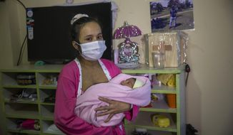 Maria Alvarez, 24, holds her newborn baby girl, standing near the wooden box that contain the cremated remains of her husband who died from the new coronavirus in June, after arriving in the home of friend who has offered her a place to stay, in Lima, Peru, Thursday, July 30, 2020. Maria, who had an asymptomatic case of COVID-19, gave birth to her first child the day before at the National Perinatal and Maternal Institute in a special ward for mothers infected with the virus. (AP Photo/Rodrigo Abd)