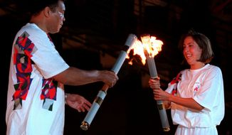 FILE - In this July 19, 1996, file photo, American swimmer Janet Evans passes the Olympic flame to Muhammad Ali during the 1996 Summer Olympic Games Opening Ceremony in Atlanta. (AP Photo/Michael Probst, File)