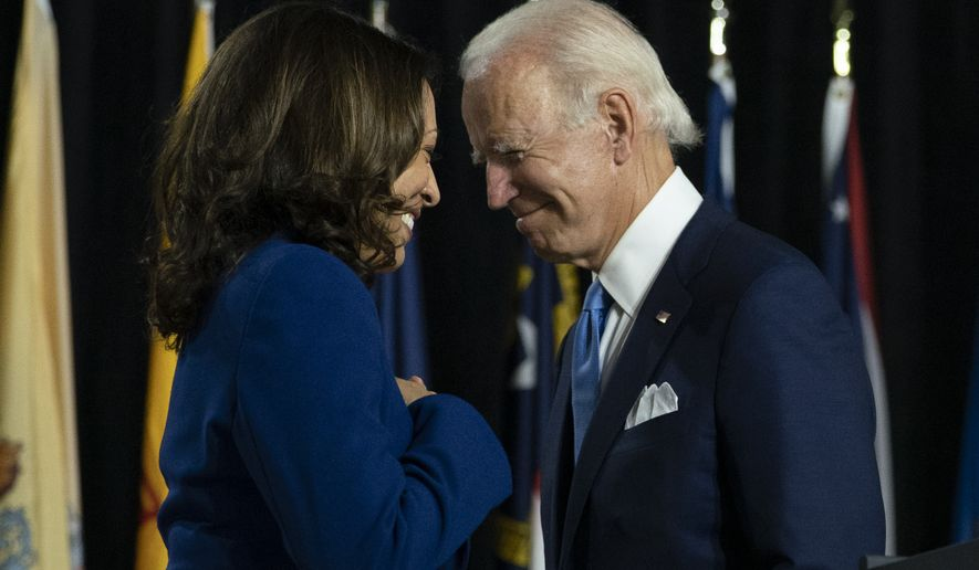 Democratic presidential candidate former Vice President Joe Biden and his running mate Sen. Kamala Harris, D-Calif., pass each other as Harris moves tot the podium. To speak during a campaign event at Alexis Dupont High School in Wilmington, Del., Wednesday, Aug. 12, 2020. (AP Photo/Carolyn Kaster)