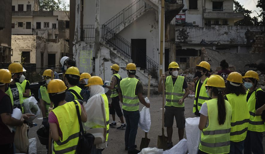 Volunteers from the American University of Beirut gather as they prepare to help remove debris in a neighborhood near the site of last week's explosion that hit the seaport of Beirut, Lebanon, Thursday, Aug. 13, 2020. (AP Photo/Felipe Dana)