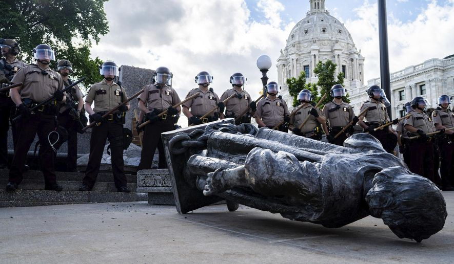 State troopers line up around a fallen statue of Christopher Columbus at the Minnesota State Capitol in St. Paul, Minn., on Wednesday, June 10, 2020. (Evan Frost/Minnesota Public Radio via AP)