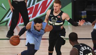 Memphis Grizzlies guard Dillon Brooks (24) drives against Milwaukee Bucks guard Donte DiVincenzo, top right, in the first half of an NBA basketball game Thursday, Aug. 13, 2020, in Lake Buena Vista, Fla. (Kim Klement/Pool Photo via AP)