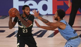 Milwaukee Bucks guard Sterling Brown (23) holds the ball away from Memphis Grizzlies forward Kyle Anderson (1) in the second half of an NBA basketball game Thursday, Aug. 13, 2020, in Lake Buena Vista, Fla. (Kim Klement/Pool Photo via AP)