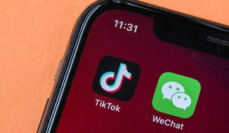 Icons for the smartphone apps TikTok and WeChat are seen on a smartphone screen in Beijing, Friday, Aug. 7, 2020. President Donald Trump has ordered a sweeping but unspecified ban on dealings with the Chinese owners of the consumer apps TikTok and WeChat, although it remains unclear if he has the legal authority to actually ban the apps from the U.S. (AP Photo/Mark Schiefelbein)