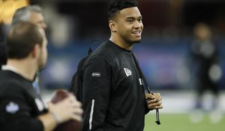 FILE - In this Feb. 27, 2020, file photo, Alabama quarterback Tua Tagovailoa watches a drill at the NFL football scouting combine in Indianapolis. Tagovailoa is happy to keep a low profile befitting his rookie status, even though he's widely hailed as the Miami Dolphins' future franchise quarterback. (AP Photo/Charlie Neibergall, File)