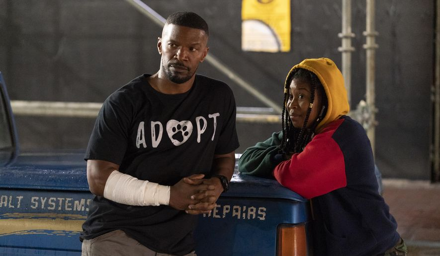 """This image released by Netflix shows Jamie Foxx, left, and Dominique Fishback in a scene from """"Project Power."""" (Skip Bolen/Netflix via AP)"""