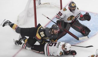 Vegas Golden Knights' William Carrier (28) and Chicago Blackhawks' Connor Murphy (5) battle as Blackhawks goalie Corey Crawford (50) looks for the puck during the third period of an NHL hockey Stanley Cup first-round playoff series, Thursday, Aug. 13, 2020, in Edmonton, Alberta. (Jason Franson/The Canadian Press via AP)