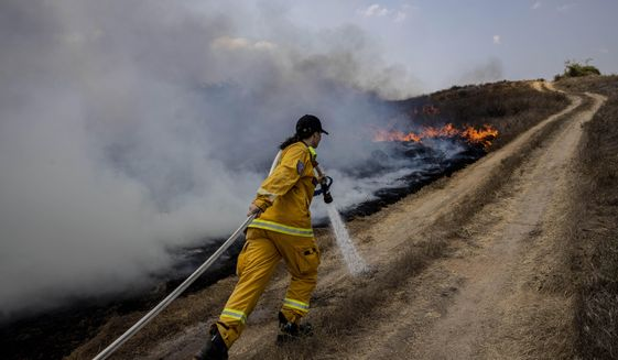 An Israeli firefighter attempts to extinguish a fire caused by a incendiary balloon launched by Palestinians from the Gaza Strip, on the Israeli side of the border between Israel and Gaza, near Or HaNer Kibbutz, Wednesday, Aug. 12, 2020. The Israeli military said it attacked a number of Hamas targets in the Gaza Strip early Wednesday in response to days of launches of explosives-laden balloons from Gaza into Israeli territory. Israel says it holds Gaza's Hamas rulers responsible for all fire emanating from the territory. (AP Photo/Tsafrir Abayov)
