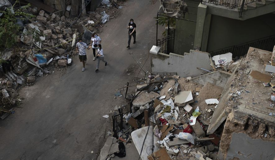 People walk next debris from destroyed buildings on a neighborhood near the site of last week's explosion that hit the seaport of Beirut, Lebanon, Thursday, Aug. 13, 2020. (AP Photo/Felipe Dana)