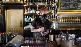 FILE - In this July 10, 2020, file photo, Davey Francis mixes drinks at Velveteen Rabbit, a cocktail bar in the Las Vegas Arts District, on the last night before they will have to close in Las Vegas. A Nevada judge says she wants proof she would have the authority to order the governor to rescind a coronavirus pandemic directive and let Las Vegas-area bars and taverns reopen. Judge Kerry Earley in Las Vegas made no immediate ruling Thursday, Aug. 13, 2020, after arguments about whether she should force Gov. Steve Sisolak to lift a bar closure order he re-imposed July 27. (AP Photo/John Locher, File)