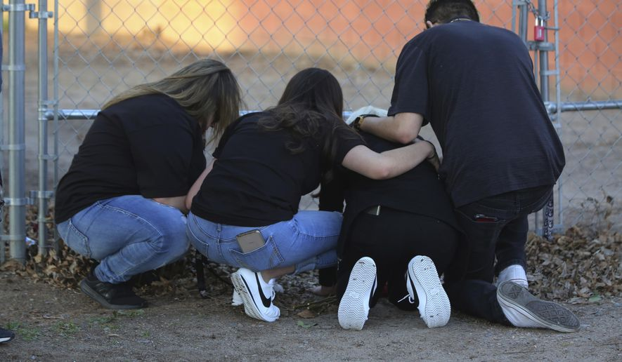 In this March 5, 2020, photo, Antonio Valenzuela's daughters, flanked by friends, kneel, at the spot their father died during an altercation with Las Cruces police on Feb. 29, 2020. An agreement announced Thursday, Aug. 13, 2020, between the city of Las Cruces and a lawyer for Valenzuela's family requires the city to provide racial bias training for police and require officers to intervene in possible excessive force episodes following Valenzuela's choking death. (Bethany Freudenthal/The Las Cruces Sun News via AP)