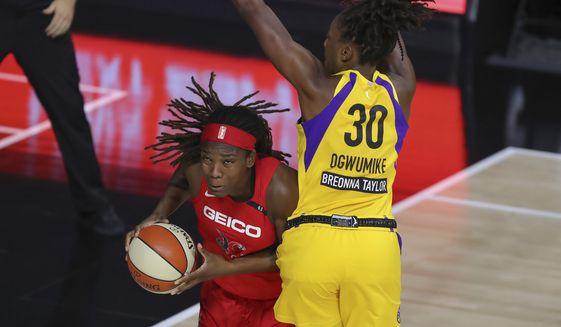 Washington Mystics' Myisha Hines-Allen ducks under the defense of Los Angeles Sparks' Nneka Ogwumike (30) during the first half of a WNBA basketball game Thursday, Aug. 13, 2020, in Bradenton, Fla. (AP Photo/Mike Carlson)