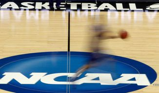 In this March 14, 2012, photo, a player runs across the NCAA logo during practice in Pittsburgh before an NCAA tournament college basketball game. (AP Photo/Keith Srakocic)  **FILE**