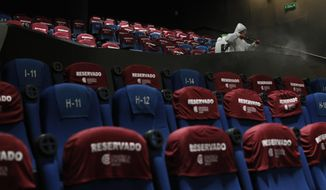 A worker disinfects a theater after a movie screening, at the Cineteca Nacional, Mexico's film archive, in Mexico City, Wednesday, Aug. 12, 2020. After being closed for nearly five months amidst the ongoing coronavirus pandemic, movie theaters in the capital reopened Wednesday at 30% capacity.(AP Photo/Rebecca Blackwell)