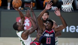 Boston Celtics' Javonte Green, left, heads to the basket past Washington Wizards' Isaac Bonga and Thomas Bryant (13) during the second half of an NBA basketball game Thursday, Aug. 13, 2020 in Lake Buena Vista, Fla. (AP Photo/Ashley Landis, Pool)