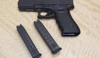 FILE - In this Tuesday, June 27, 2017, file photo, a semi-automatic hand gun is displayed with a 10 shot magazine, left, and a 15 shot magazine, right, at a gun store in Elk Grove, Calif. A three-judge panel of the 9th U.S. Circuit Court of Appeals has thrown out California's ban on high-capacity ammunition magazines. The panel's majority ruled Friday, Aug. 14, 2020, that the law banning magazines holding more than 10 bullets violates the constitutional right to bear firearms. (AP Photo/Rich Pedroncelli, File)