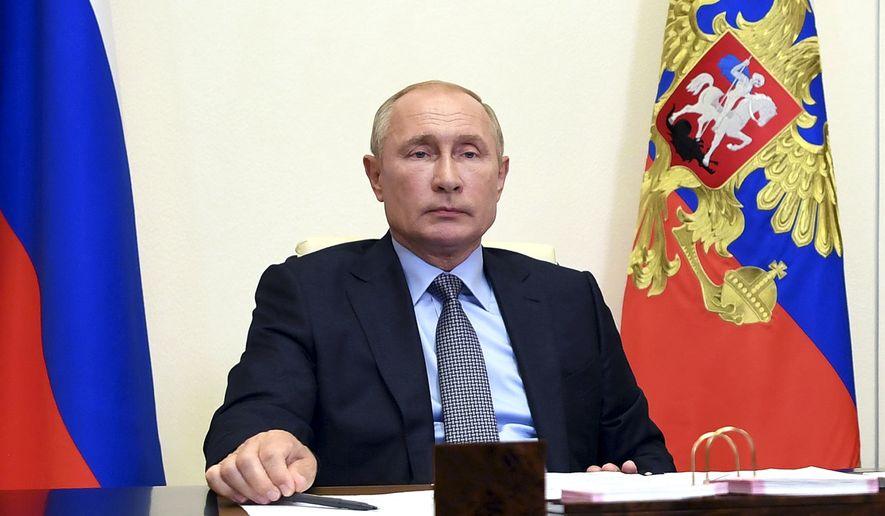 Russian President Vladimir Putin attends a meeting via video conference at the Novo-Ogaryovo residence outside Moscow, Russia, Friday, Aug. 14, 2020. (Alexei Nikolsky, Sputnik, Kremlin Pool Photo via AP)